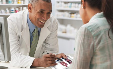 A pharmacist educates his patient during a consultation using the iMD Health Patient Engagement Platform.