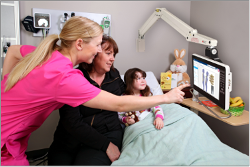 Hospital nurse shows patient in bed how to use digital bedside screen